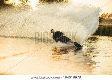 Man wakeboarding on a lake with splashes of water. Wakeboarder surfing across the lake showing off is skill.