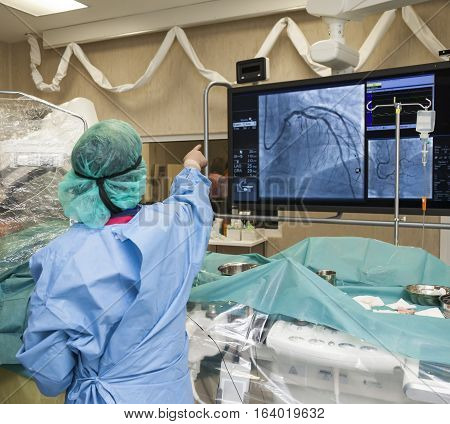 A surgeon with his back to the camera is pointing to a monitor during surgery in modern hospital.