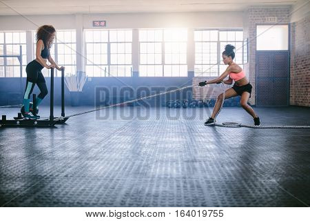 Fitness sled pull with female standing on sled. Two women doing intense physical workout at gym.