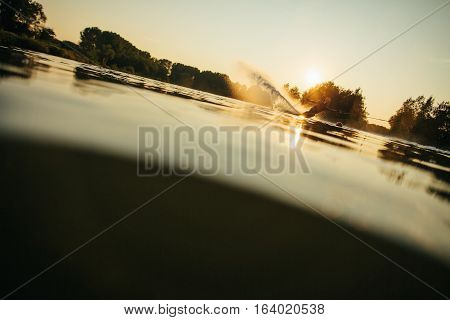 Low angle shot of man wakeboarding on a lake. Water skiing at sunset.