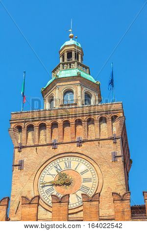 Close up of Accursi tower is also known as the Clock Tower of Palazzo d'Accursio or Comunale, Piazza Maggiore, Bologne in Italy in the blue sky.