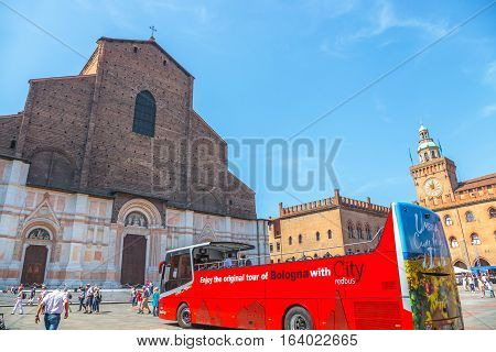 Bologna, Italy - May 28, 2016: City Red Bus, the tourist bus service to explore Bologna city, and Balisica of San Petronio on the Piazza Maggiore, the largest church built in bricks in the world.