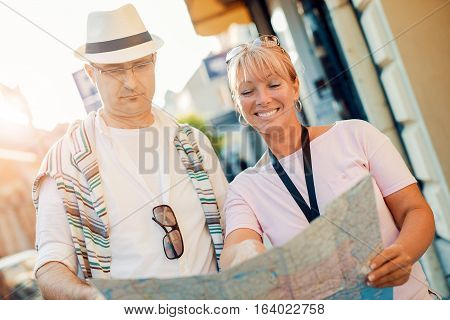 Mature couple using a city map for location in the town.Mature man and woman standing together outdoors in city with a map.