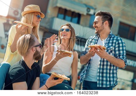 Close-up of four young cheerful people eating pizza outdoors.They are laughing and eating pizza and having a great time.