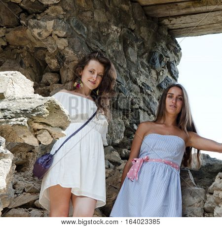 young pretty women of cute smiling girls in blue and white dress at old ruined stony building of broken historical ancient ruins with stone walls sunny day outdoor