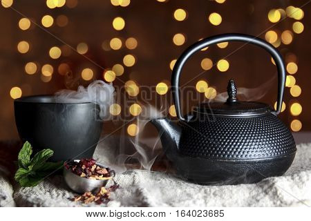 Smoking hot tea in black ceramic pot with black cup And bokeh background