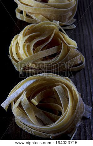 Low light photographed tagliatelle pasta on wooden table with white flour