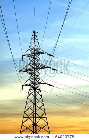 High-voltage power supply line metal tower on beautiful sunset vertical view