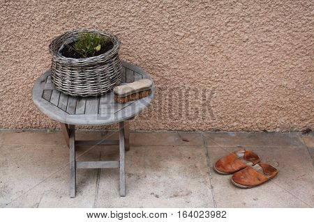 Vintage things:old French garden wooden folding table, wicker basket with flowers, old bright brown leather slippers, shoe brush with stiff bristles, background - yellow pink walls. Provence. France