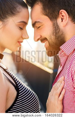 Side view of couple's faces. Lady's hand on man's chest. Nothing will break us apart.