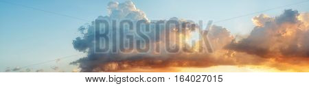 Pastel color heavenly cloud pano at sunset against light blue gradient