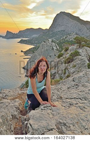 The girl sits on a high hill by the sea at sunset. Sudak. Crimea