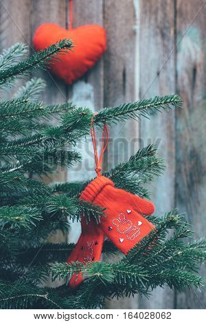 red children's mittens hanging on the branches of spruce and red plush heart on a wooden background tinted photo