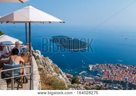 People in a restaurant above Dubrovnik.  Dubrovnik, Croatia - July 18, 2015: Two men and one woman in a restaurant on top of the mountain above Dubrovnik.  Summer view of Dubrovnik.