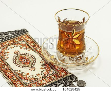 Turkish tea with traditional turkish carpet on white background