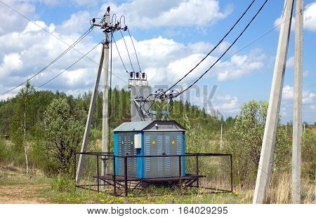 Transformer of rural power supply line in countryside in summer day