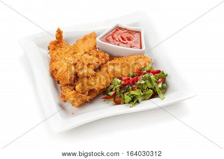 Fried chicken breast fillet in batter with vegetable salad on the plate . Isolated on white background.