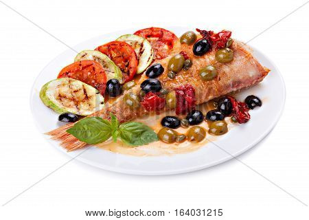 Grilled fish with grilled vegetables on a plate isolated on white background