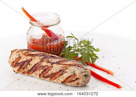 Grilled Kebab with Red Sauce on a Plate. Isolated on White Background.