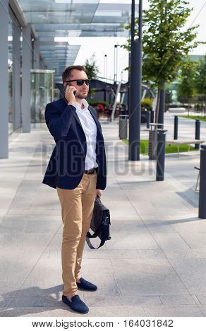 Businessman walking down the street with a briefcase talking on a cell phone