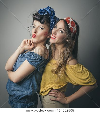 Three quarter body portrait of two happy young female friends in retro clothing smiling and pouting lips studio background