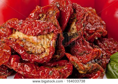 Sun-dried tomatoes on a ripe tomatoes background