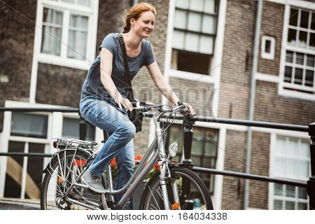 Smiling young woman cycling on a city bicycle in an old European town.