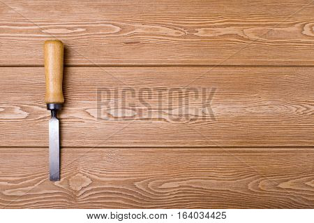 Chisel with wooden handle on a wood background