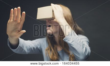 Surprised or shocked woman using cardboard VR goggles. Shallow DOF focus on the hand.