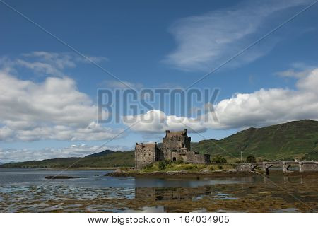 Majestic Eilean Donan castle on beautiful autumn day. with sunny foreground dramatic sky and amazing scenery