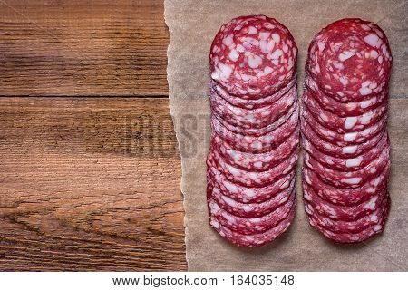 Sausage cut into circles on the paper. Natural wooden background. Blank space. View from above