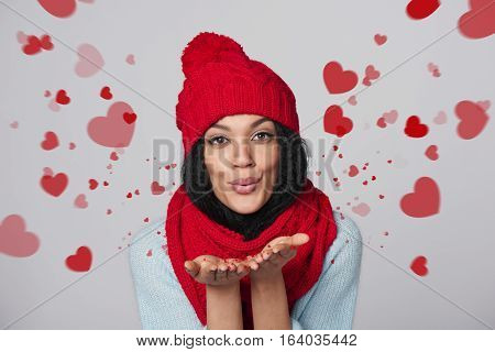 Happy mixed race african american - caucasian woman blowing a kiss with hearts over gray background