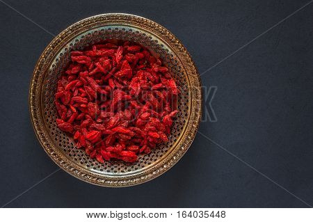 Raw dried goji berries on a vintage metal plate on a black background