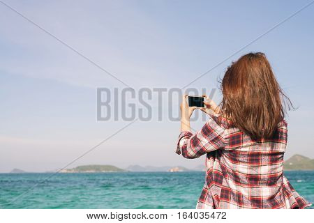 Back view of a woman taking photograph with a smart phone camera at the horizon on the beach.