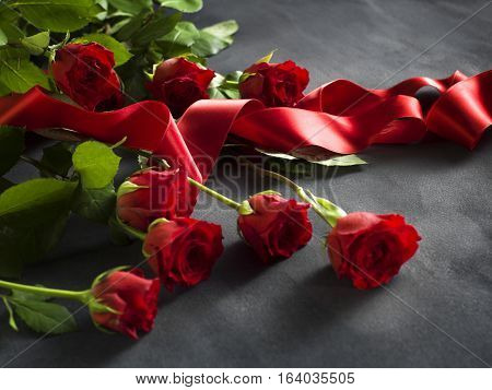 Ribbon and grey stone with a bunch of red roses