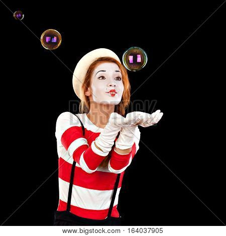 Portrait of the female mime comedian catches bubbles isolated on black background