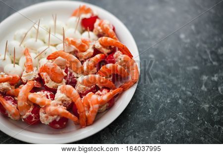 Shrimp tails with filled eggs on white plate with toothpicks