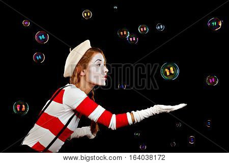 Portrait of the female MIM comedian catches bubbles isolated on black background