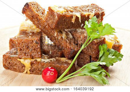 Snack roast rusk from dark bread with cheese on wooden board.