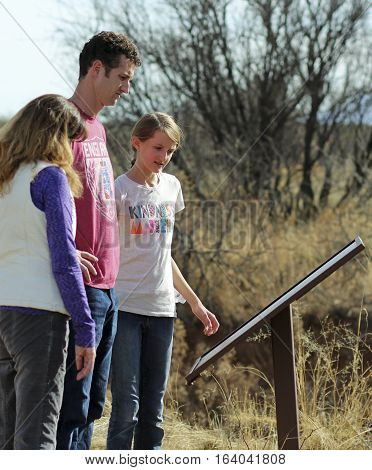 SIERRA VISTA, ARIZONA, DECEMBER 20. The Murray Springs Clovis Site on December 20, 2016, east of Sierra Vista, Arizona. A family reads a sign at the Murray Springs Clovis Paleoindian Site where ancient human artifacts and woolly mammoths from 13000 years