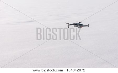 Small grey modern drone hovering against white snow