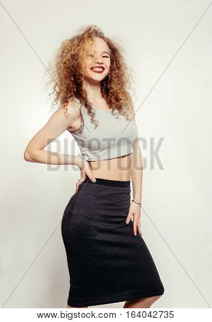 people youth and beauty concept - Beauty young woman with curly big and long hair. Permed hair. Glamour lady Beauty Girl on grey background. Beautiful Woman Portrait. Blond Wavy Hair. Girl Smile