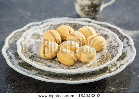 Sweet and delicious russian walnut cookies (stuffed with dulce de leche) on grey porcelain plate, espresso on the background. Dark table. Selective focus. Natural light.