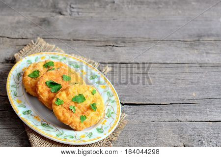 Fried pea cutlets on a plate and on a wooden background with copy space for text. Hearty cutlets cooked with boiled dried peas, eggs, flour and spices. Diet dish idea. Closeup