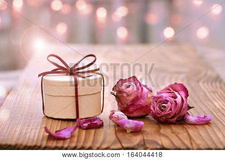 Romantic still life on wood with dried rose blossom and a gift for Mothers Day or Valentines Day
