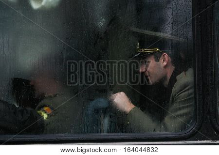 BUCHAREST ROMANIA - DECEMBER 1 2010: A military is seen behind a bus window during a military parade. More than 3000 soldiers and personnel from security agencies take part in the massive parades on National Day of Romania.