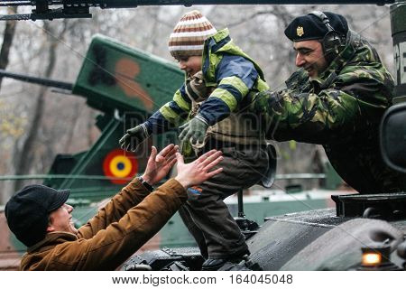 BUCHAREST ROMANIA - DECEMBER 1 2010: A child is playing on a tank during a military parade on National Day of Romania. More than 3000 soldiers and personnel from security agencies take part in the massive parades on National Day of Romania.