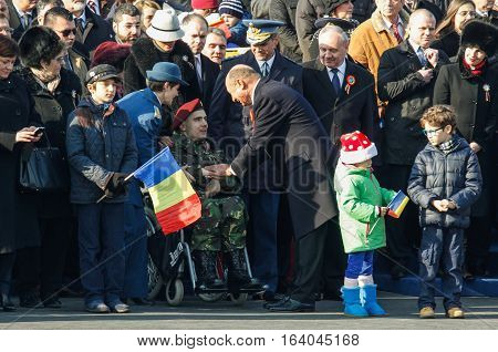 BUCHAREST ROMANIA - DECEMBER 1 2013: Romanian president Traian Basescu salutes a war veteran during a military parade on National Day of Romania. More than 3000 soldiers and personnel from security agencies take part in the massive parades on National Day