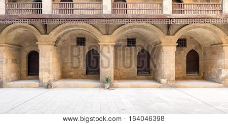 Facade of the ground floor of caravansary (Wikala) of Bazaraa showing four arches four wooden doors and small windows of accommodation rooms surmounted by wooden balustrades, Cairo, Egypt