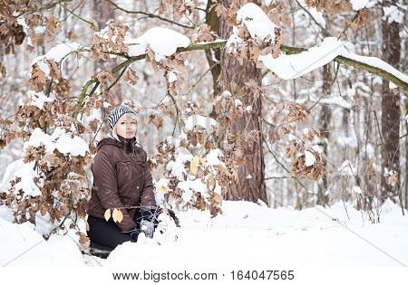 Girl sitting near the branch with oak leaves in the winter forest.